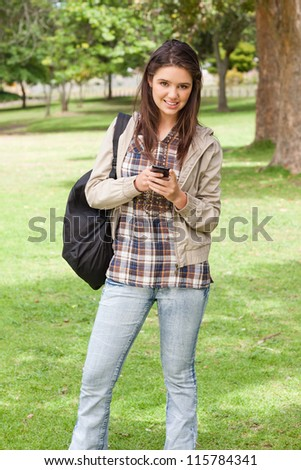 Young student posing while using a smartphone in a park