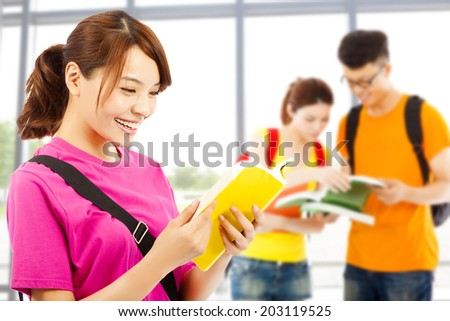 young student read a  book  with classmates at school - stock photo