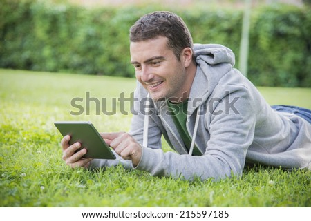 young student reading and relaxing with tablet on the grass - stock photo