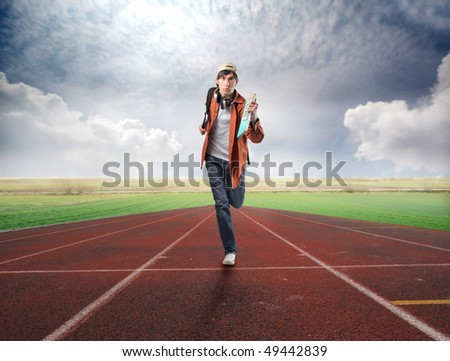 Young student running on a racing track - stock photo