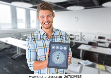 Young student showing tablet pc against classroom - stock photo