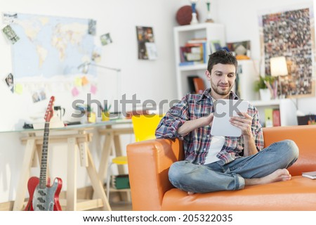 young student sits on a sofa is using a digital tablet at home - stock photo