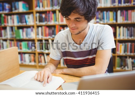 Young student sitting at desk reading a book in college library - stock photo