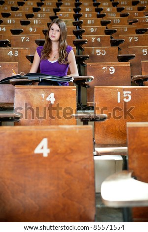 Young student sitting in empty lecture hall - stock photo