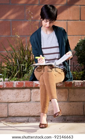 Young student sitting on brick wall in backyard with textbook - stock photo