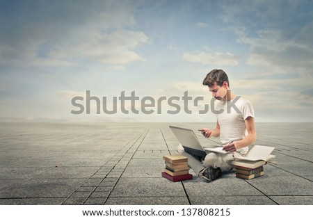 young student sitting on the ground with telephone, laptop and many books