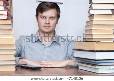 Young student sitting with book on the head between books