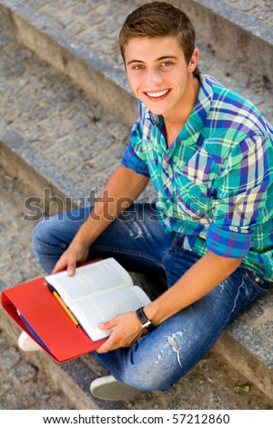 Young student sitting with books - stock photo