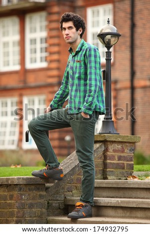young student standing in college yard - stock photo