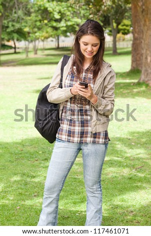 Young student standing while using a smartphone in a park - stock photo