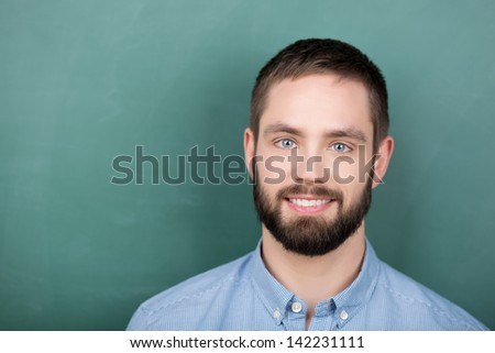 Young student stands in front of a Chalkboard - stock photo