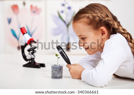 Young student studies small plant in elementary science class - stock photo