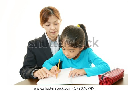 Young student studying with teacher - stock photo