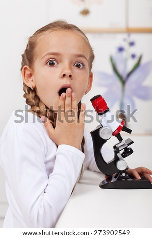 Young student surprised of what she saw on the microscope - miracles of nature sciences - stock photo