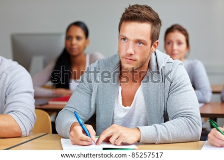 Young student taking notes in university class - stock photo