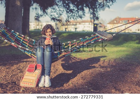 Young student texting/using phone in hammock - stock photo