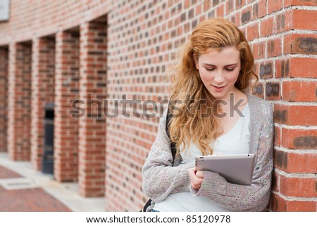 Young student using a tablet computer outside a building - stock photo