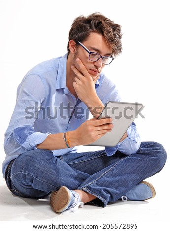 Young student using a tablet on white background.Young man sitting down using tablet computer. - stock photo