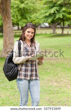 Young student using a touch pad in a park - stock photo