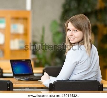 Young student using computer in a library. looking at camera