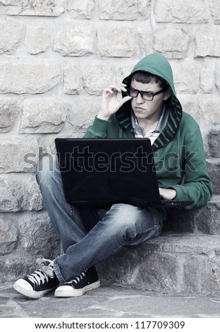 Young student using laptop on the steps - stock photo