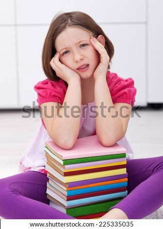 Young student with a headache - having lots to learn from many books - stock photo