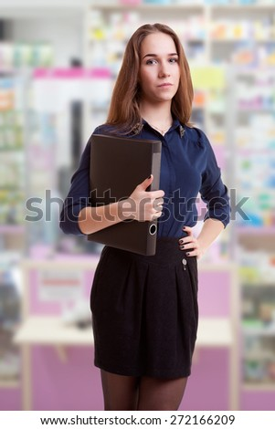 Young student with folder in her hand in pharmacy. Studio shooting. School and success in studying - stock photo
