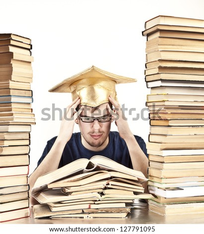 young Student with Graduation cap learning at home between tall stacks of books in the form of skyscrapers