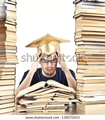 young Student with Graduation cap learning at home between tall stacks of books in the form of skyscrapers - stock photo