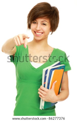 Young student with her books in hand pointing at you, isolated on white background - stock photo