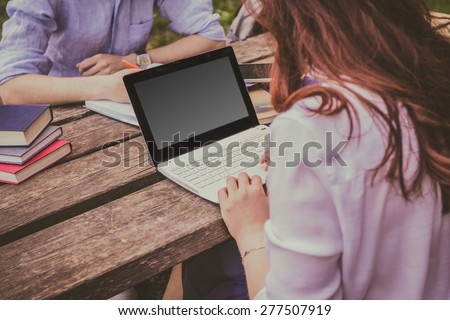 Young student woman taping on laptop in a city park on a wooden table and a young student man writing in a journal.Young student outdoors with laptop and tablet.Life style.City - stock photo