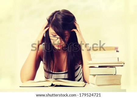 Young student woman with lots of books studing for exams.