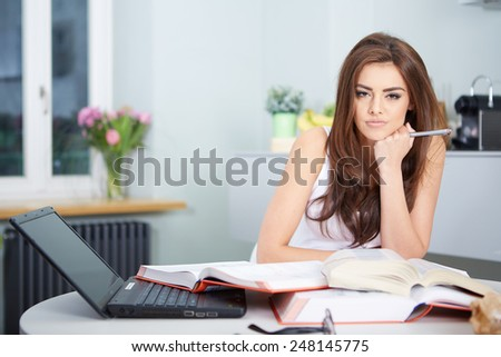 Young student woman with lots of books studying for exams