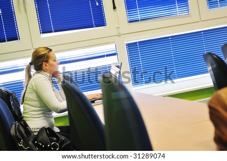young student  woman working on notebook at university classroom