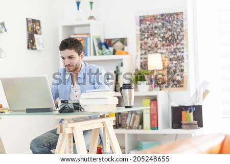 young student works on his laptop at home - stock photo