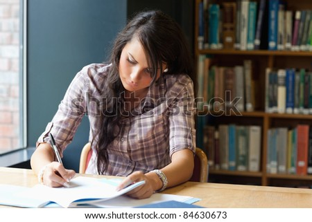 Young student writing in a library - stock photo
