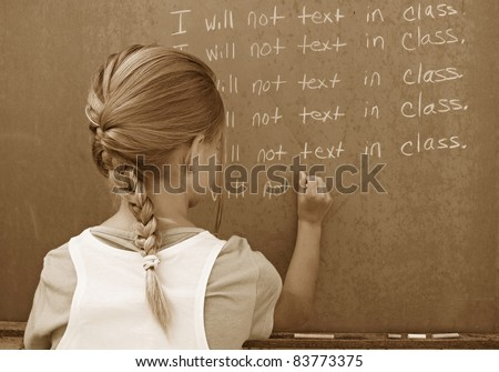 young student writing lines on chalkboard