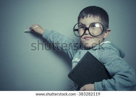 young student writing on a blackboard school with a book in hand and big glasses - stock photo