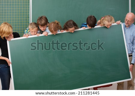 Young students and their two teachers standing holding a blank blackboard all peering over the top to see what will be written there - stock photo