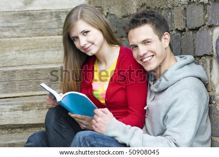 Young students are reading book together. - stock photo