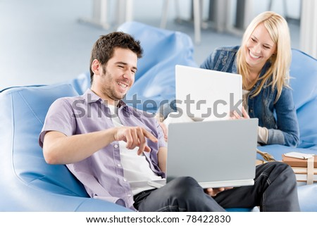 Young students at high-school relaxing pointing at laptop - stock photo