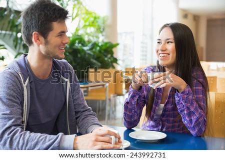 Young students having coffee together at the university - stock photo