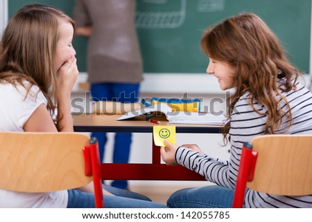 Young students laughing and holding smiley note during the class - stock photo