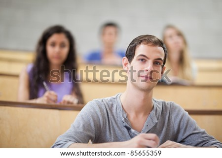 Young students listening during a lecture with the camera focus on the foreground - stock photo