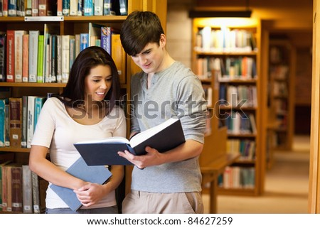 Young students reading a book in a library