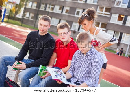 Young students reading books at the school playing field.