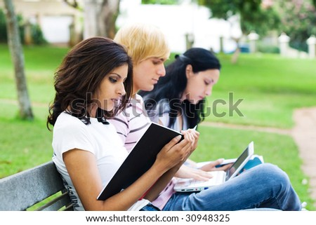 young students reading books on park bench - stock photo