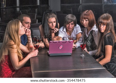 Young students relaxing with laptop and wine in cafe - stock photo