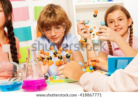 Young students studying molecular structure at lab - stock photo