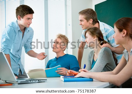 young students studying together in a classroom - stock photo